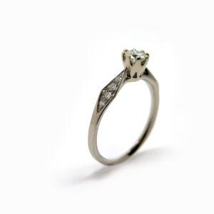 Solitaire fin en or blanc dont les côtés sont pavés de petits diamants