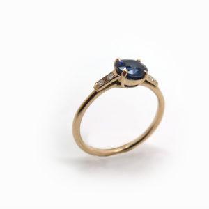 Solitaire fin en or rose orné d'un saphir ovale et épaulé de diamants
